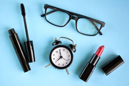 Black glasses, alarm clock, mascara and red pomade on blue background composition. Flat lay and top view photo Stok Fotoğraf