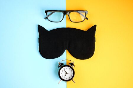 Black glasses, alarm clock and sleep mask on blue and yellow background composition. Flat lay and top view photo Banco de Imagens
