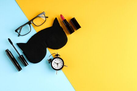 Black glasses, alarm clock, mascara, pomade and sleep mask on blue and yellow background composition. Flat lay and top view photo