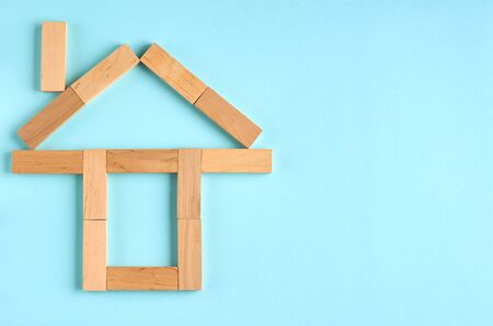 Brown wooden blocks house shape idea on blue background composition. Flat lay and top view photo Stok Fotoğraf