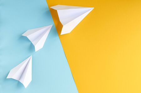 White paper planes on blue and yellow background composition. Flat lay and top view photo Stok Fotoğraf
