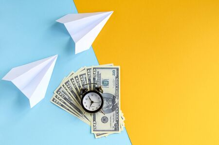 White paper planes, alarm clock and money on blue and yellow background composition. Flat lay and top view photo