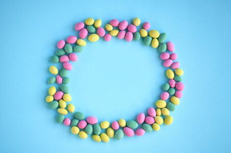 Colored sweets, peanut covered with glaze on blue background composition, round shape, frame. Flat lay and top view photo