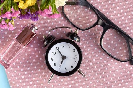 Alarm clock, black glasses and perfume bottle on napkin background composition. Flat lay and top view photo
