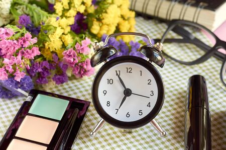 Alarm clock with flowers, mascara and perfume bottle on napkon background composition. Flat lay and top view photo