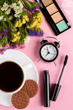 Coffee cup with cookies, alarm clock, flowers, mascara, on pink background composition. Flat lay and top view photo Stok Fotoğraf
