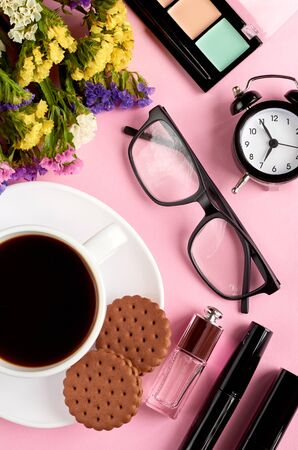 Coffee cup with cookies, alarm clock, flowers, mascara and glasses on pink background composition. Flat lay and top view photo