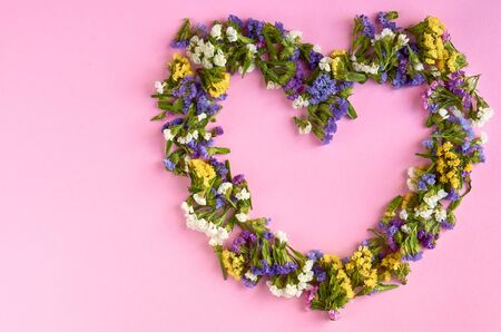 Colored flowers on pink background composition, heart shape. Flat lay and top view photo