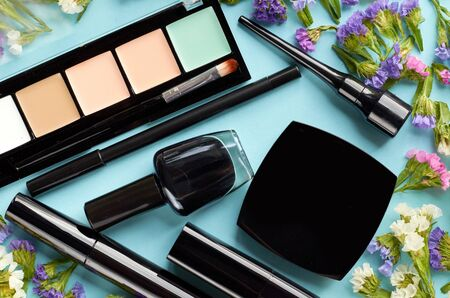 Makeup objects with colored flowers on blue background composition. Flat lay and top view photo