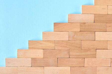 Brown wooden blocks stairs shape idea on blue background composition. Flat lay and top view photo Stok Fotoğraf
