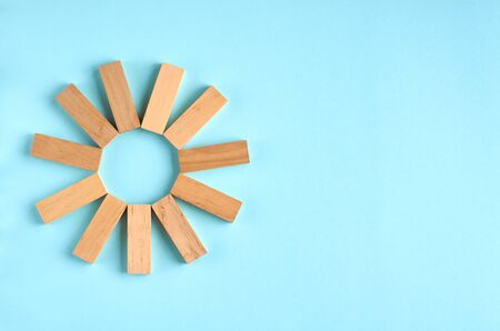 Brown wooden blocks sun or star shape idea on blue background composition. Flat lay and top view photo