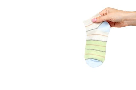 Hand with striped cotton sock, child footwear. Isolated on white background. Copy space template.