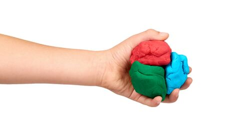 Children hand with color plasticine, kids educational toy. Isolated on white background.