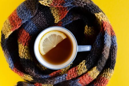Woolen scarf with tea cup and lemon slice composition on yellow background. Flat lay, layout and tabletop mockup with copy space.