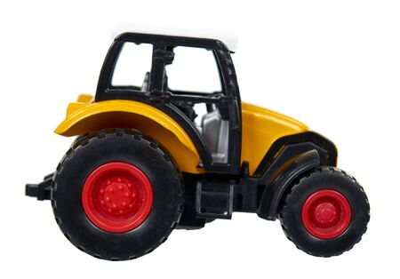 Yellow plastic traktor toy. Farming vehicle, harvest equipment. Isolated on white background.