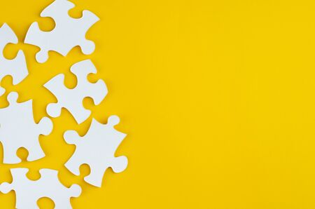 White puzzles composition on yellow background. Flat lay, layout and tabletop mockup with copy space.