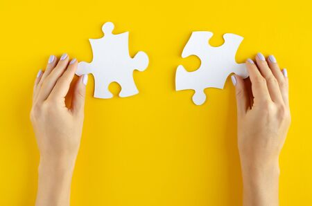 Hand with puzzles composition on yellow background. Flat lay, layout and tabletop mockup with copy space. Banco de Imagens