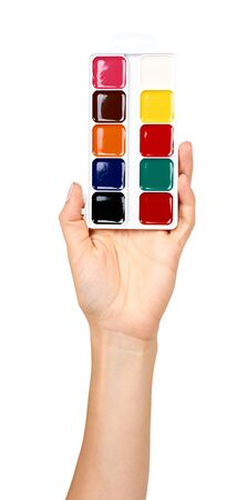 Hand with palette with watercolors. Multicolor paints, draw supply. Isolated on white background.