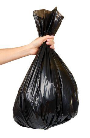 Hand met zwarte plastic vuilniszak, gebonden rommelpakket, vuilnispakket. Geïsoleerd op een witte achtergrond. Stockfoto
