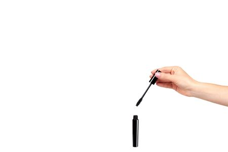 Hand with black mascara, eye makeup brush. Isolated on white background. Copy space template.