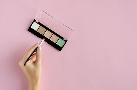 Hand with makeup shadows palette composition on pink background. Flat lay, layout and tabletop mockup with copy space.
