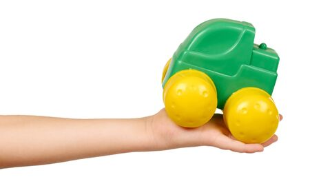Kids hand with plastic green toy car with big yellow wheels. Isolated on white background.