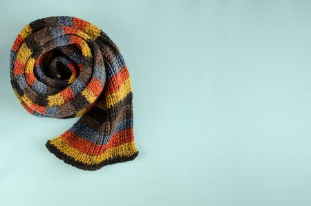 Woolen scarf composition on blue background. Flat lay, layout and tabletop mockup with copy space.