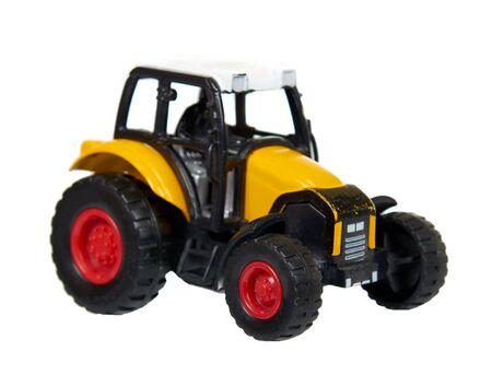 Yellow plastic traktor toy. Farming vehicle, harvest equipment. Isolated on white background.