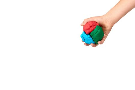 Children hand with color plasticine, kids educational toy. Isolated on white background. Copy space template, mockup.
