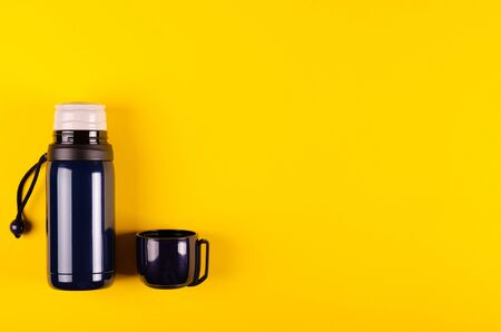 Dark thermos composition on yellow background. Flat lay, layout and tabletop mockup with copy space.