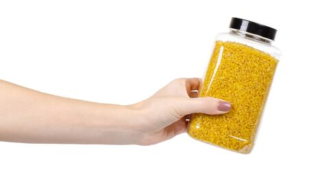 Hand with raw bulgur grain in plastic container, healthy cereal, whole wheat. Isolated on white background.
