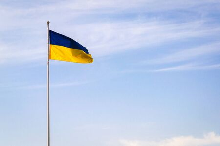Blue yellow flag of Ukraine against the sky. Fabric develops in the wind.