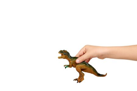 Kid hand with rubber dinosaur toy. Prehistoric wild animal, danger beast, T-Rex. Isolated on white background. Copy space.