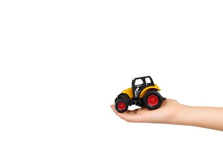 Kids hand with yellow plastic traktor toy. Farming vehicle, harvest equipment. Isolated on white background. Copy space.