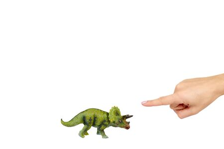 Green rubber dinosaur toy with hand, prehistoric wild animal. Isolated on white background. Copy space.