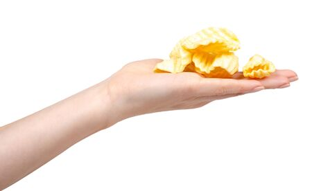 Hand with yellow corrugated potato chips. Isolated on white background. Stock Photo