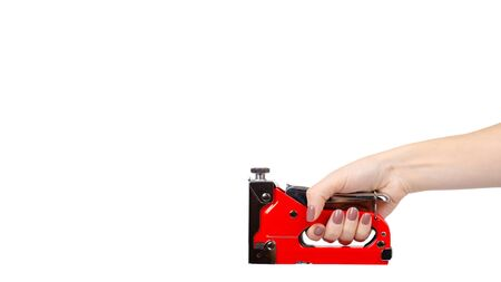 Hand with red industrial stapler, furniture industry hardware. Isolated on white background. Copy space, template.