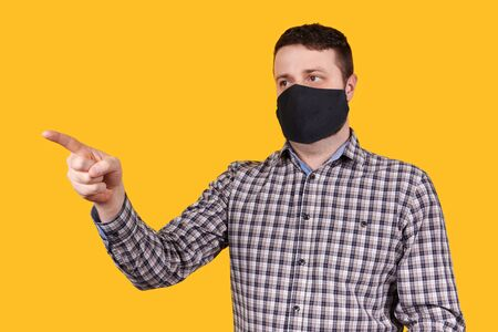 Man in black face mask pointing with finger, isolated on orange background. Coronavirus concept. Stock Photo
