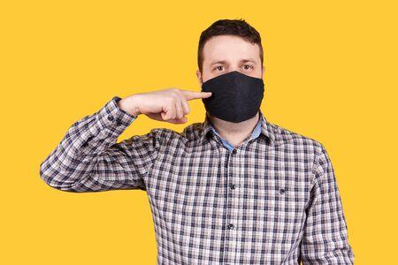 Man pointing on black face mask, isolated on orange background. Coronavirus concept.