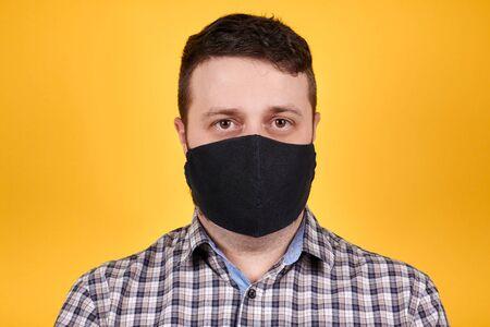 Man in black face mask looking at camera, isolated on orange background. Coronavirus concept. Stock Photo