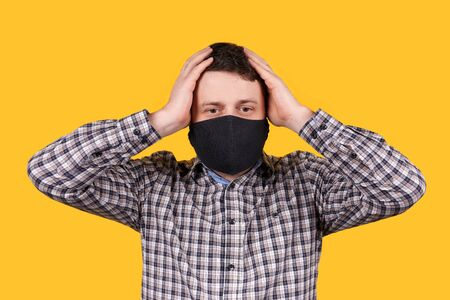 Man in black face mask holding his head with hands, panic, isolated on orange background. Coronavirus concept.
