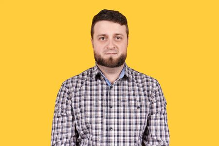 Man with beard looking at camera, isolated on yellow backgorund. No emotions.