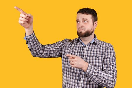 Man pointing with both hands. Isolated on orange background.