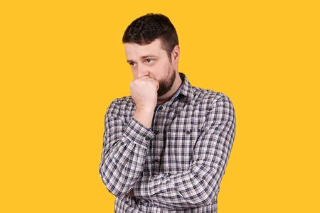 Man with beard holding his head with hand, panic, isolated on orange background. Troubles concept.