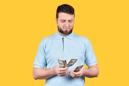 Man count paper money, dollars. Isolated on orange background.