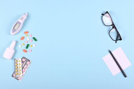 Medical pills, thermometer, eyeglasses and spray bottle on blue background, flat lay, overhead view image. Medicine concept. Stock Photo