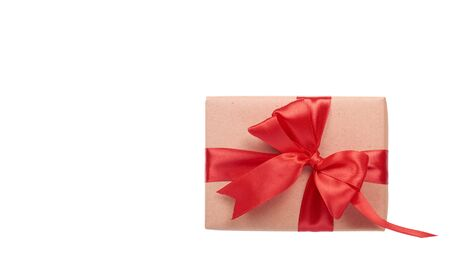Gift box wrapped with brown paper. Isolated on white background. Copy space, template.
