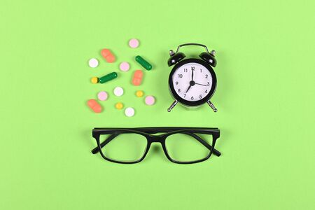 Medical pills, glasses and clock on green background, flat lay, overhead view image. Time to use drugs concept.