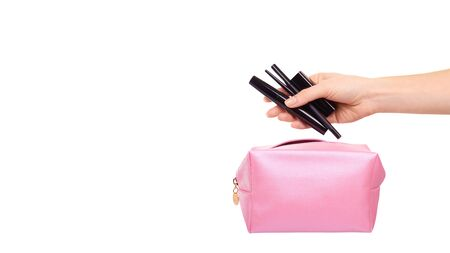 Hand with pink makeup bag. Glamour cosmetic accessory. Isolated on white background. Copy space, template.