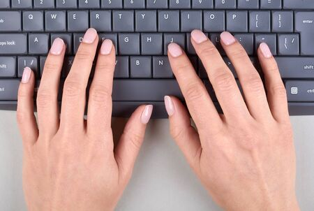 Hands with keyboard on grey background. Flat lay, overhead view image.